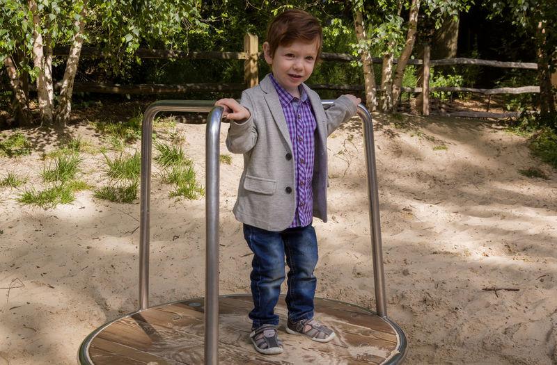Cute boy standing on merry-go-round at playground