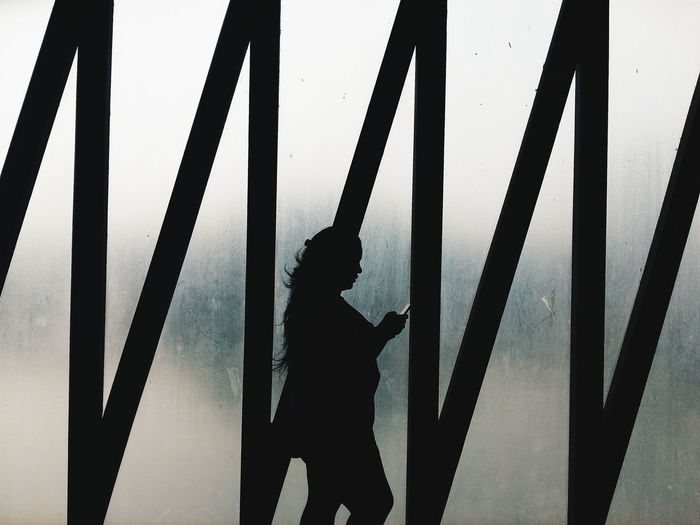 Silhouette woman walking against frosted glass