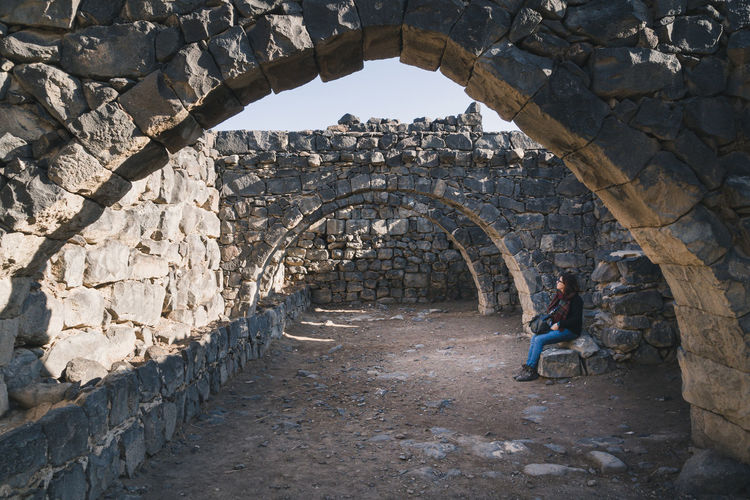 Full length of woman sitting by stone wall
