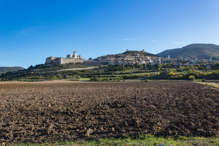 Assisi Autumn Basilica Church Field Saint Francis Of Assisi Agriculture Architecture Building Exterior Built Structure Clear Sky Day Field Growth History Italy Landscape Mountain Nature No People Outdoors Rural Scene Sky Town Umbria