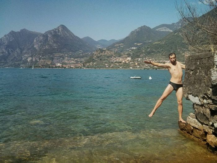Full length of shirtless man standing in sea against mountains