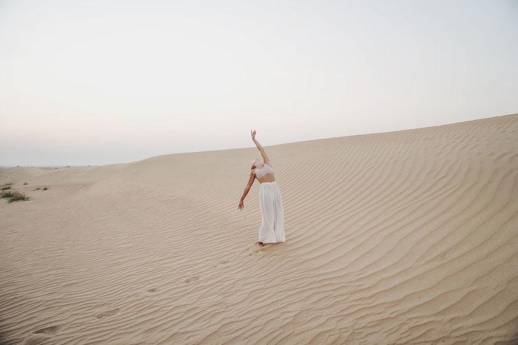 Woman walking on sand dune in desert against sky