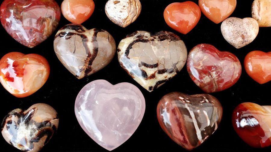 Close-Up Of Heart Shaped Gemstones Over Black Background