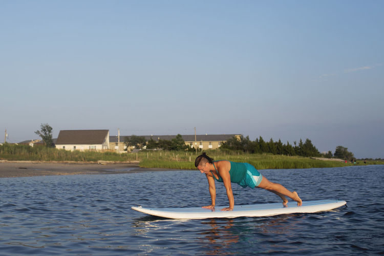 Woman surfing in lake against clear sky