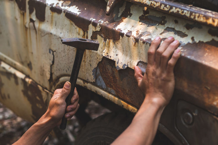 Hand holding a pickup truck hammer rusty peeling paint tires old car wheels vintage