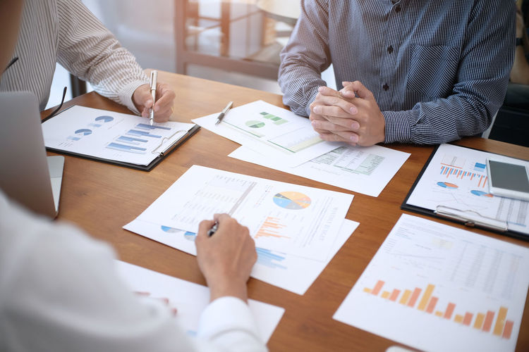 Midsection of business people working on graphs on table in office