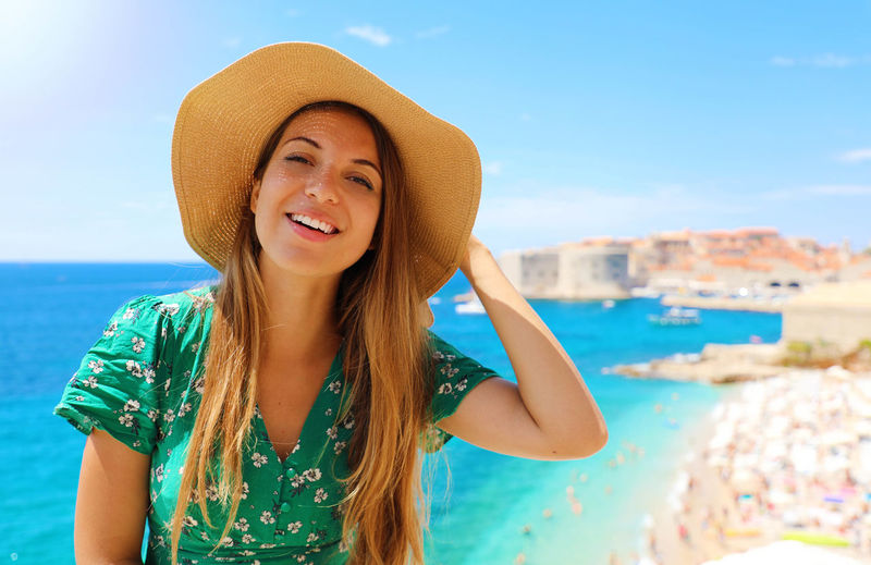 Portrait of smiling young woman against sea against sky