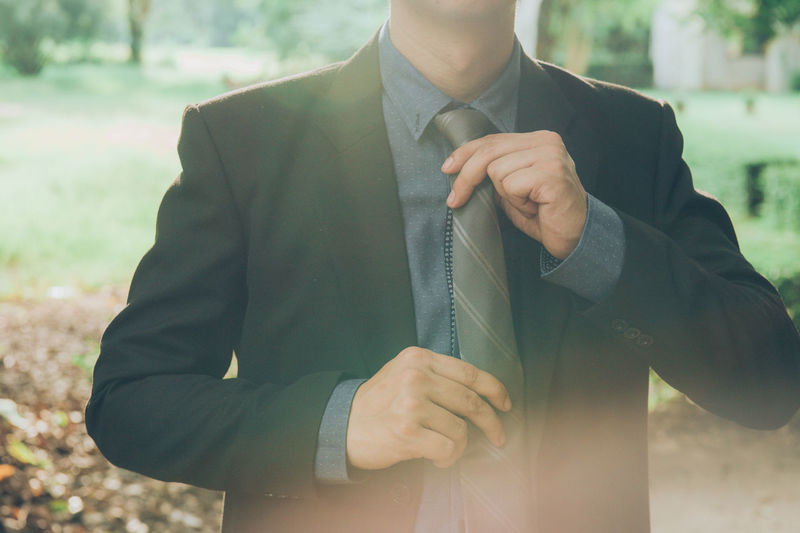 Close-up of businessman holding tie