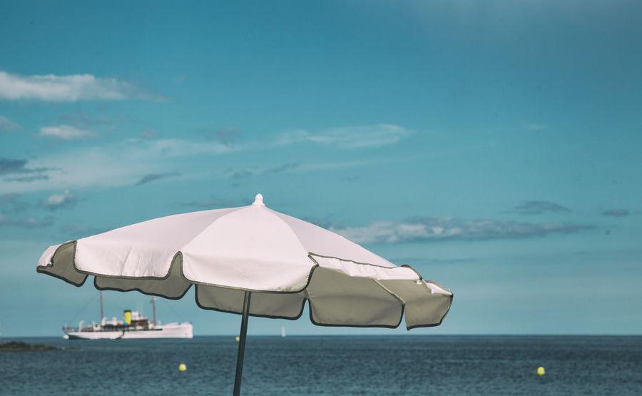 The Traveler - 2018 EyeEm Awards Beach Beach Umbrella Beauty In Nature Cloud - Sky Day Horizon Horizon Over Water Land Nature No People Outdoors Parasol Scenics - Nature Sea Shade Sky Tranquil Scene Tranquility Umbrella Water