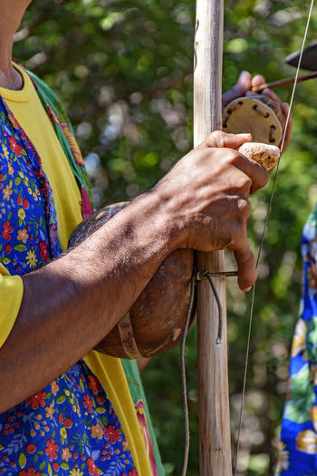 Berimbau player playing his instrument during typical folk festival in the interior of Brazil African Brazil Music Adult Berimbau Brazilian Culture Day Ethnic Folk Folklore Hand Holding Human Body Part Human Hand Instrument Leisure Activity Lifestyles Men Musical Instrument Musician Occupation One Person Outdoors Real People