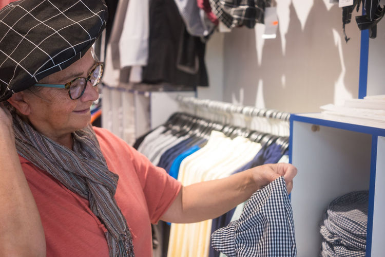 Senior woman wearing cap buying clothes at store