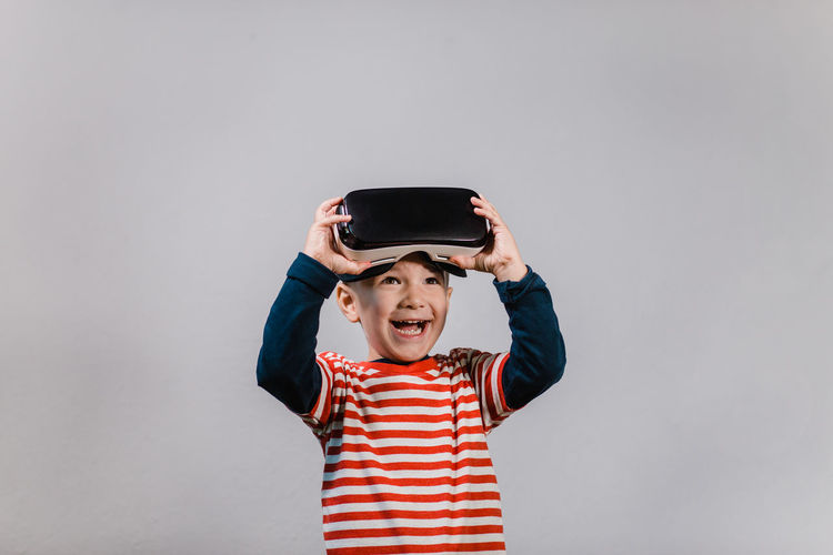 Smiling happy boy enjoying virtual reality with VR glasses. Portrait of cheerful child wearing virtual reality headset against grey background. Child Front View Striped Mouth Open One Person Indoors  Vr Virtual Reality Portrait Boy Red Color Headset Glasses Caucasian Technology Preschool Isolated Gadget Digital E-learning 3D Horizontal Education Hands Spread Having Fun