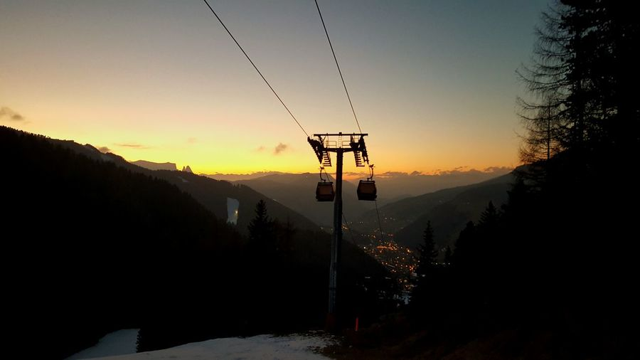 Low angle view of ski lift by mountains against sky during sunset