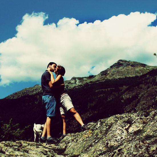 Low angle view of couple kissing while standing on rock formation against cloudy sky