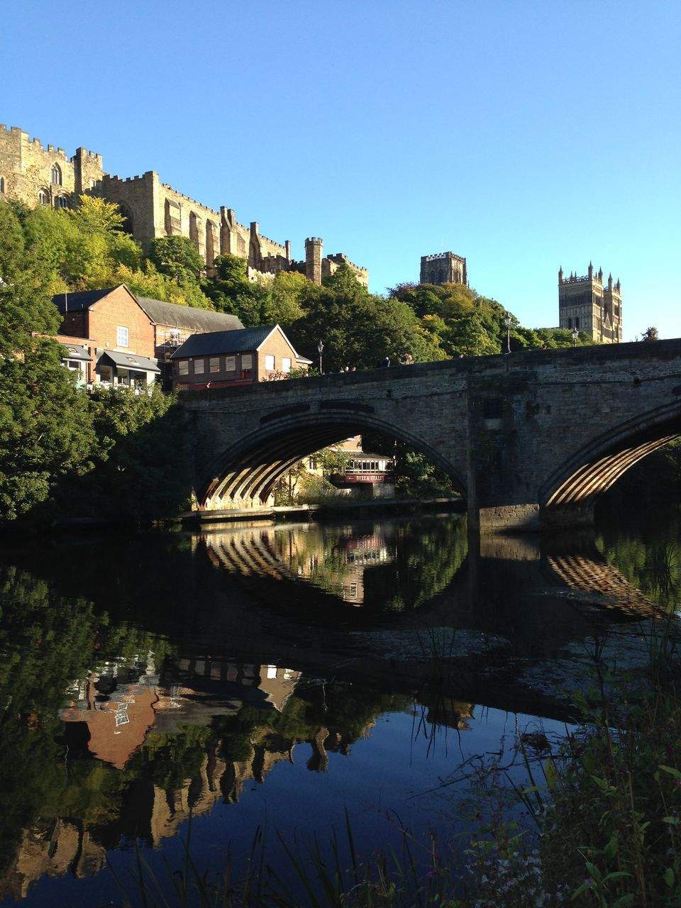 Arch Bridge Over River By Durham Cathedral Against Clear Sky