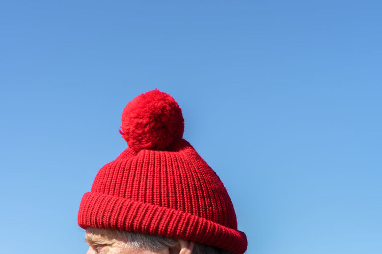 Cropped Image Of Man Wearing Red Knit Hat Against Clear Blue Sky