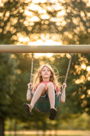 Portrait of smiling girl on swing in playground