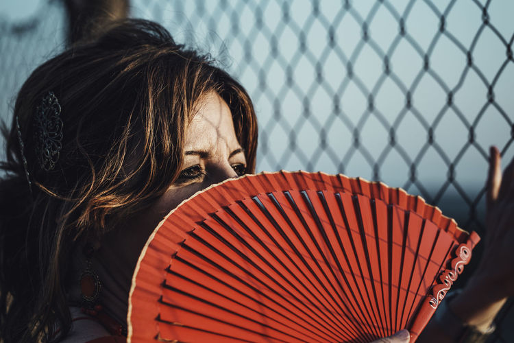 Close-up of woman holding hand fan