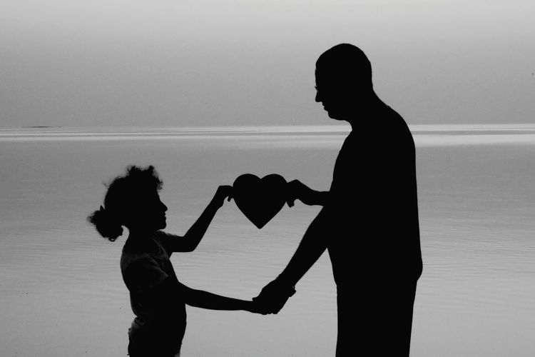 Silhouette father and daughter holding heart shape against sea