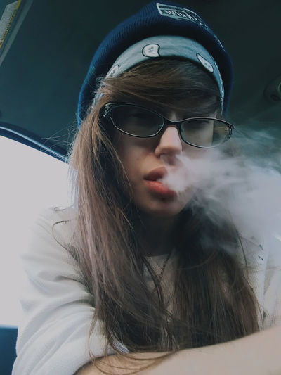 Portrait Of Young Woman Smoking In Car
