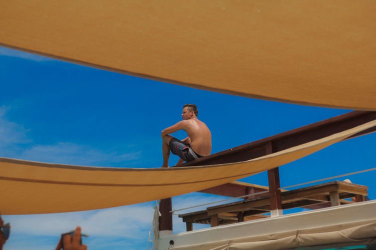 Low angle view of shirtless man sitting on pier against blue sky