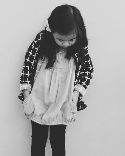 Little Girl With Hands In Pockets Standing Against Wall
