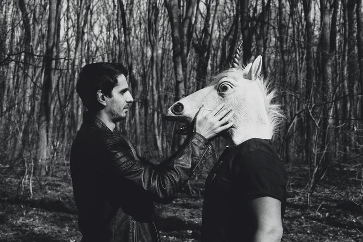 Side view of man standing with male friend wearing horse mask in forest