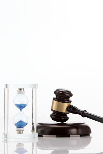 Close-Up Of Gavel With Hourglass Against White Background