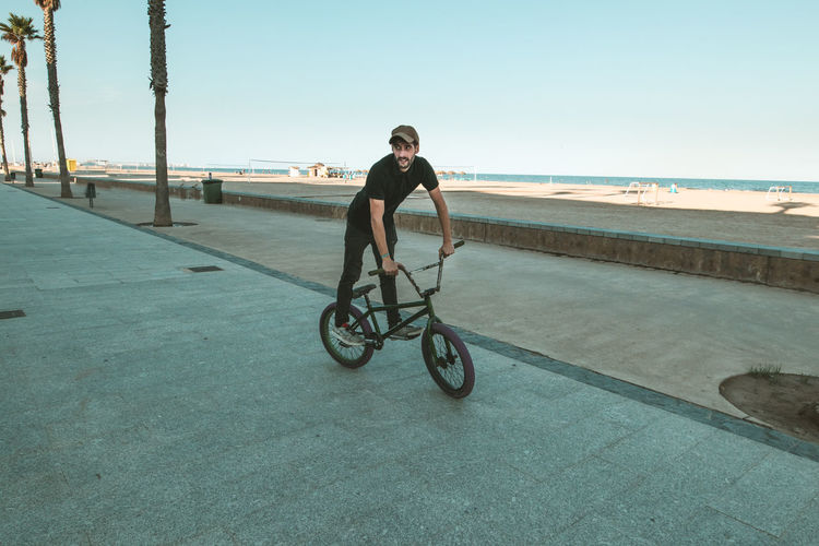 Man riding bicycle on sea against clear sky
