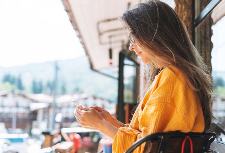 Side view of woman using smart phone outdoors