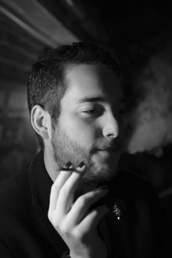 Close-Up Of Young Man Smoking In Darkroom