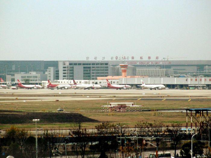 Airplane on airport runway against sky in city