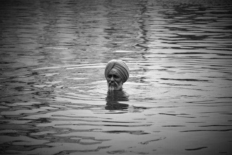 Man wearing turban swimming in lake