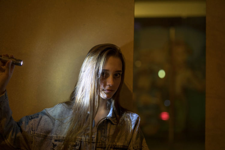 Portrait of beautiful young woman holding flashlight while standing against wall