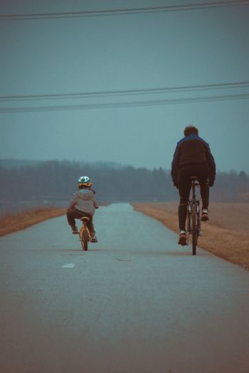 Rear View Of Man And Child Riding Bikes