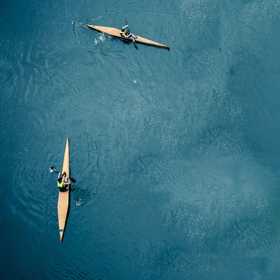 High Angle View Of People Canoeing In Sea