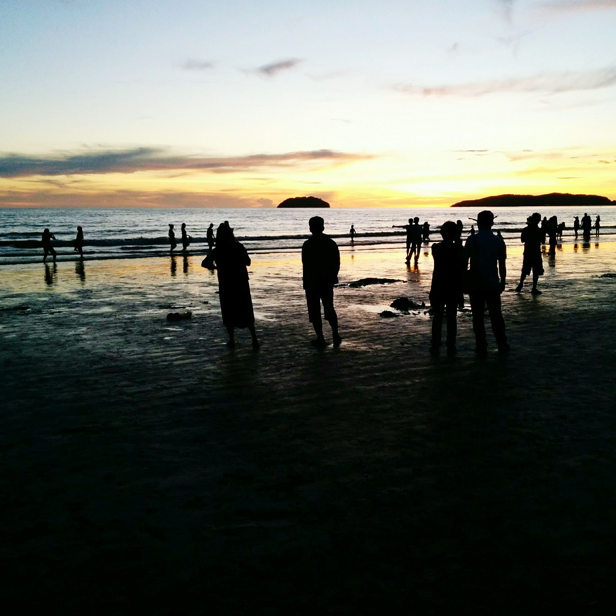 beach, sunset, silhouette, water, nature, sea, large group of people, leisure activity, sky, lifestyles, beauty in nature, scenics, real people, sand, outdoors, horizon over water, women, vacations, men, beach volleyball, day, people, adult