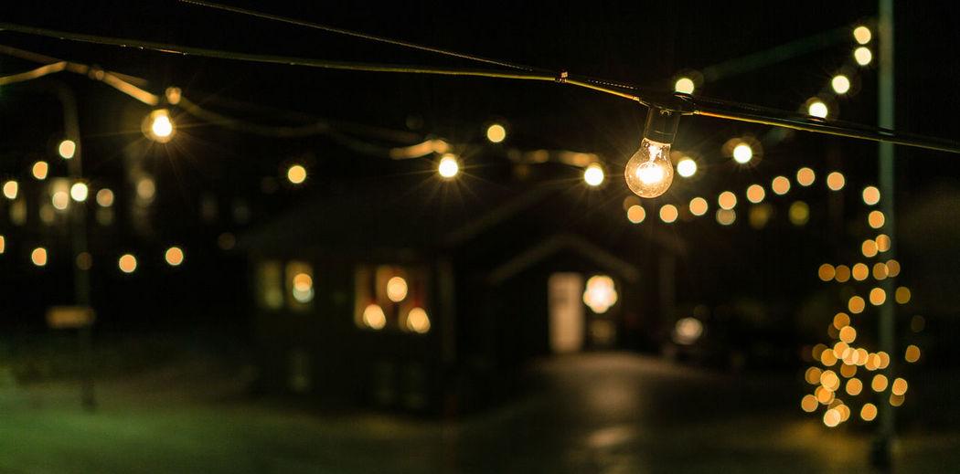 Defocused lights on illuminated street light at night