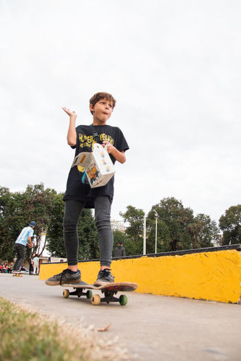 Full length of boy skateboarding on skateboard against sky