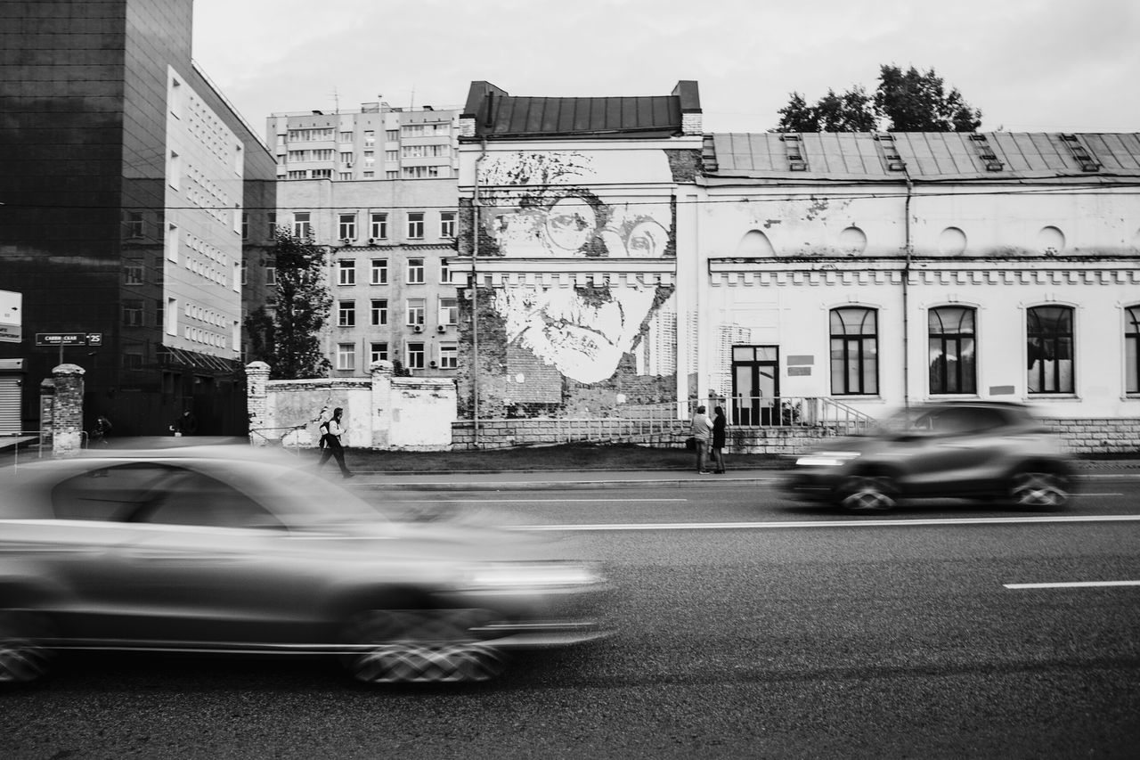 blurred motion, speed, car, motion, architecture, transportation, building exterior, built structure, city, mode of transport, land vehicle, city street, street, road, city life, day, outdoors, sky, no people