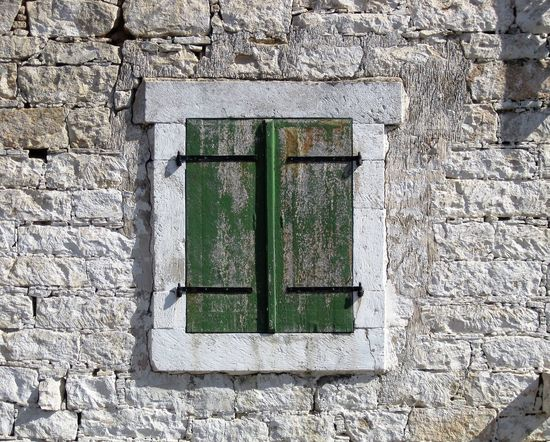 Green wooden closed window shutters with metal hinges set in a painted brick wall on a Cyprus village house. Architecture Brick Wall Background Brick Work Building Exterior Close-up Green Green Shutters Metal Hinge Window Wooden Window Shutters The Architect - 2018 EyeEm Awards