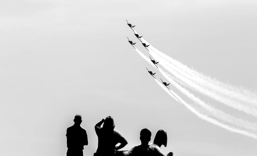 Airplane Air Vehicle Sky Transportation Flying Mode Of Transportation Airshow on the move Low Angle View Group Of People Motion Real People Mid-air Travel Lifestyles Fighter Plane Nature People Silhouette Copy Space Teamwork Plane Outdoors Order Air Force Blackandwhite Black And White Black & White Skyporn Skyporn Competition Clouds Clouds And Sky