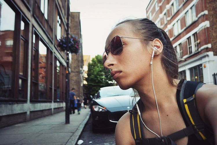 Thoughtful beautiful woman looking away while listening to music in city