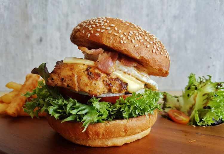 Chicken burger served on a wooden boardwith french fries and green salad Food Ready-to-eat Bread Healthy Eating Hamburger Chicken Burger Fast Food Nutrition Diet Colesterol Calories Green Salad