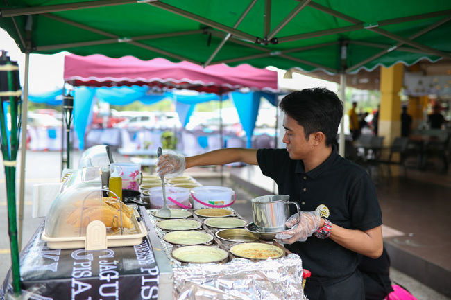 A Man preparing griddle pancake, a snack of crispy flour and egg mixture and layered with finely chopped nuts and sugar on hot pan from burning fire stove. A popular Malay street food, apam balik. Apam Balik Business Dessert Dessert Food Hot Hot Pan Malay Malay Food Occupation One Person Pancake Preparing Preparing Food Small Business Street Food Sweet Food Traditional Working