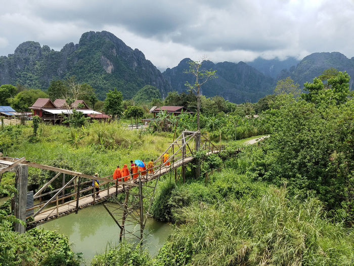 Buddhist monks cross a bridge in Laos Hills Tropical Forest Karst On Foot Monks Buddhist Laos Vang Vieng Orange Robes Crossing The River Peaks Mountains Nature Landscape_photography Travel Wooden Bridge EyeEmNewHere Tree Mountain Agriculture Sky Cloud - Sky Mountain Range Growing Farmland Lush - Description First Eyeem Photo