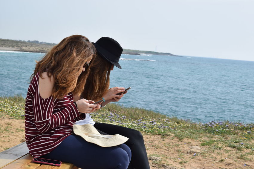 Beach Casual Clothing Cellphone Clear Sky Communication Phone Holding Horizon Over Water Leisure Activity Lifestyles Mobile Phone Nature One Person Outdoors Photographing Portable Information Device Real People Sea Smart Phone Sitting Technology Using Phone Water Wireless Technology Women
