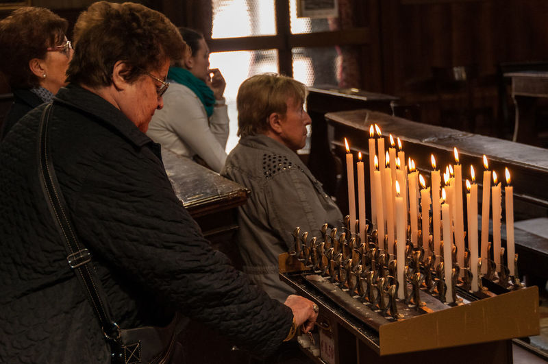 Lighting candles in a Church Candle Church Indoor Lifestyles Lighting Candle Lowlightphotography People Pray Religion
