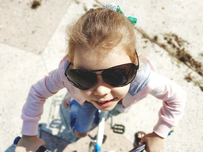 High Angle Portrait Of Smiling Girl Wearing Sunglasses Cycling During Sunny Day