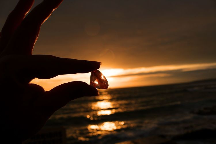 Cropped hand of woman holding diamond against sea at sunset